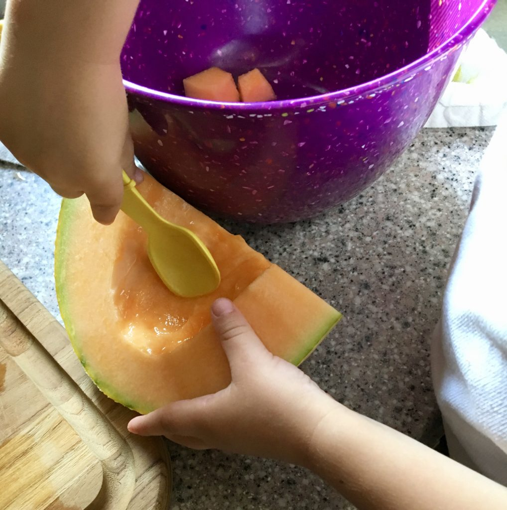 a child scoops seeds from a cantaloupe